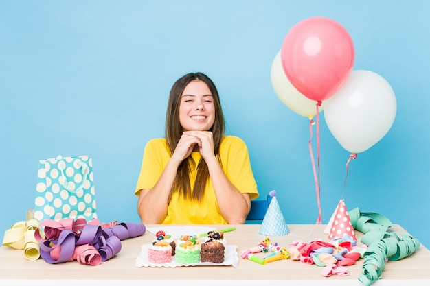La mujer caucásica joven que organiza un cumpleaños mantiene las manos debajo de la barbilla, está mirando felizmente a un lado.