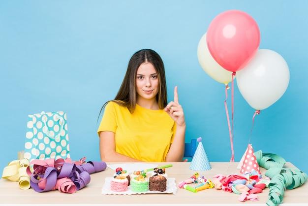 Mujer caucásica joven que organiza un cumpleaños que muestra el número uno con el dedo.