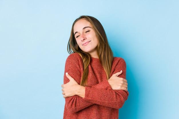 Mujer caucásica joven que presenta abrazos aislados, sonriendo despreocupado y feliz.
