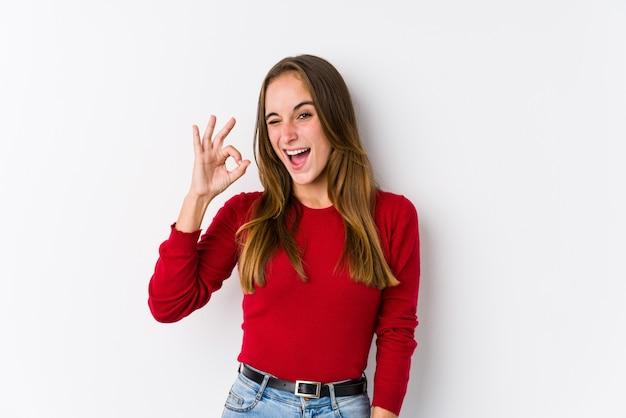 La mujer caucásica joven que presenta guiña un ojo y sostiene un gesto aceptable con la mano.