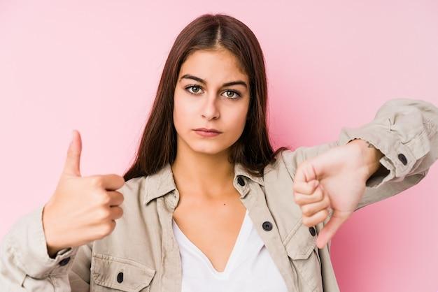 Mujer caucásica joven que presenta en una pared rosada que muestra los pulgares arriba y los pulgares abajo