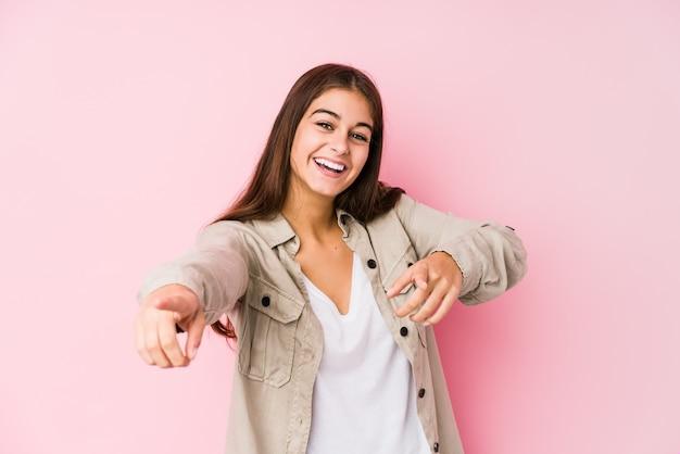 Mujer caucásica joven que presenta en una pared rosada sonrisas alegres que señalan al frente.