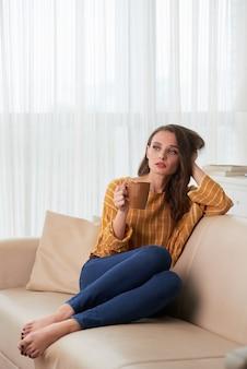 Mujer caucásica joven que se relaja en el sofá en casa con la taza