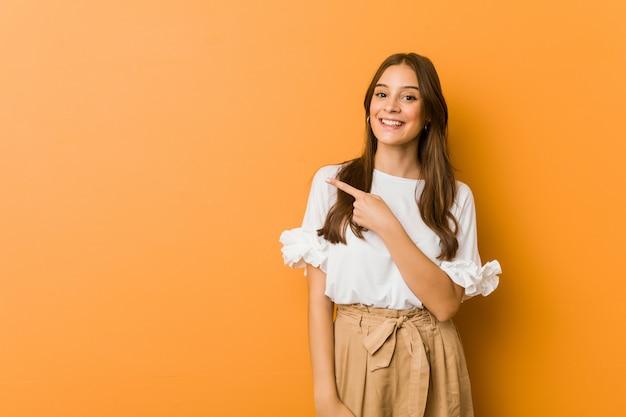 Mujer caucásica joven que sonríe y que señala a un lado, mostrando algo en el espacio en blanco.