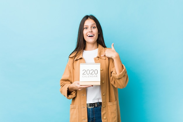 La mujer caucásica joven que sostenía un calendario 2020 sorprendió apuntándose a sí mismo, sonriendo ampliamente.