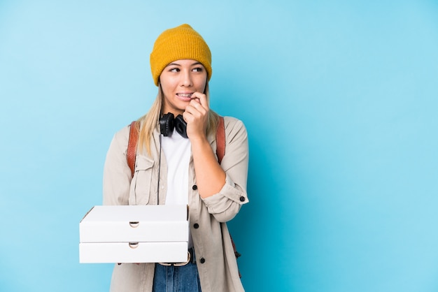 La mujer caucásica joven que sostenía las pizzas aisló el pensamiento relajado sobre algo que miraba un espacio de la copia.