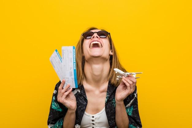 Mujer caucásica joven que sostiene boletos aéreos muy feliz