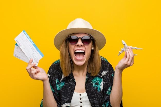 Mujer caucásica joven que sostiene boletos de avión muy felices.