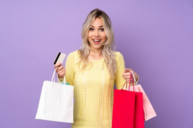 Mujer caucásica joven que sostiene bolsos de compras sobre la pared púrpura