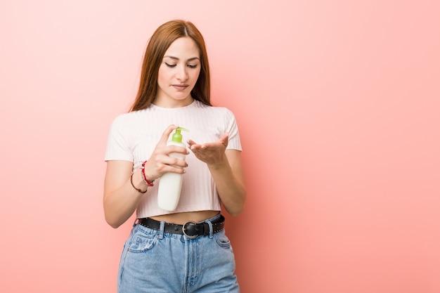 Mujer caucásica joven que sostiene una botella de crema