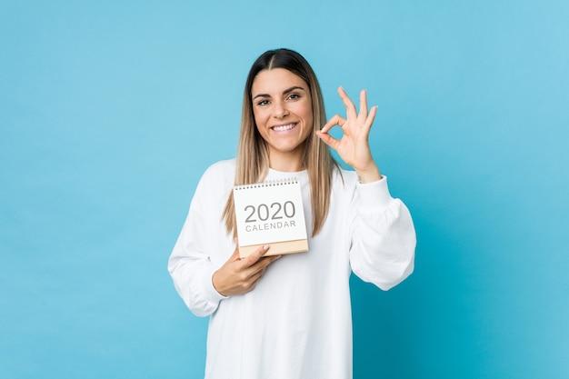 Mujer caucásica joven que sostiene un calendario 2020 alegre y confidente que muestra gesto aceptable.