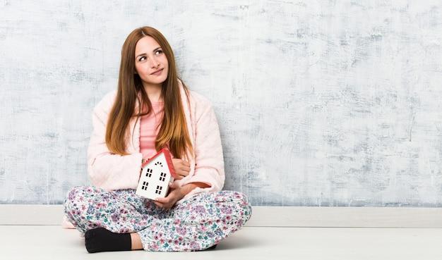 Mujer caucásica joven que sostiene una casa y una sonrisa confiada con los brazos cruzados.