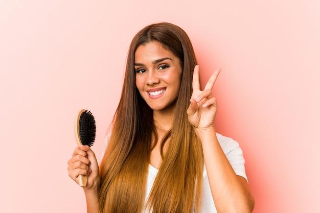 Mujer caucásica joven que sostiene un cepillo para el pelo que muestra la muestra de la victoria y que sonríe ampliamente.