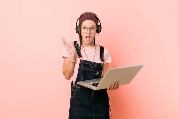 Mujer caucásica joven que sostiene una computadora portátil que celebra una victoria o el éxito
