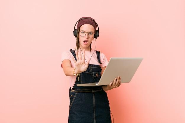 Mujer caucásica joven que sostiene una computadora portátil que se coloca con la mano extendida que muestra la señal de stop, previniéndole.