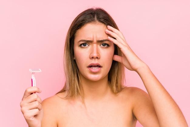 Mujer caucásica joven que sostiene una cuchilla de afeitar aislada mujer caucásica joven que sostiene un cepillo para el pelo aislado sorprendida, ha recordado una reunión importante. <mixto>