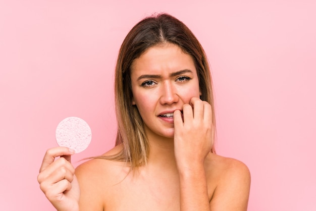 Mujer caucásica joven que sostiene un disco facial aislado mordiendo las uñas, nervioso y muy ansioso.