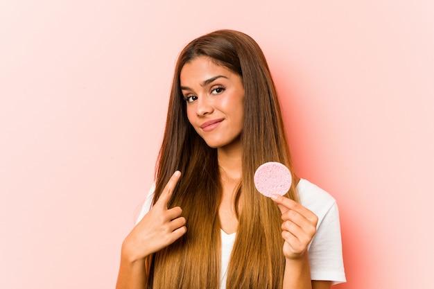 La mujer caucásica joven que sostiene una esponja facial que señala con el dedo en usted como invitando se acerca.