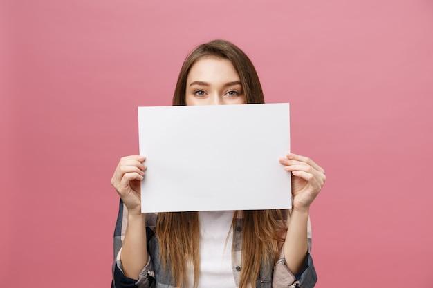 Mujer caucásica joven que sostiene la hoja del papel en blanco