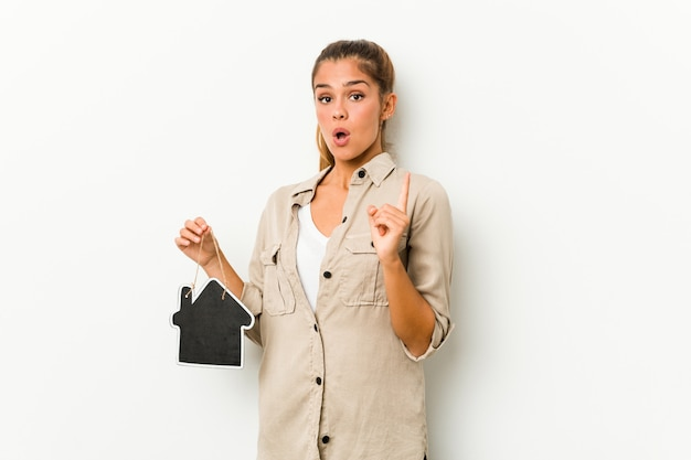 Mujer caucásica joven que sostiene un icono de la casa que tiene una gran idea, concepto de creatividad.