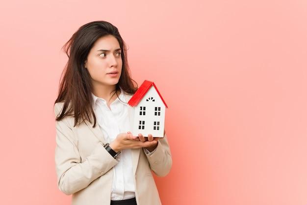 Mujer caucásica joven que sostiene un icono de la casa