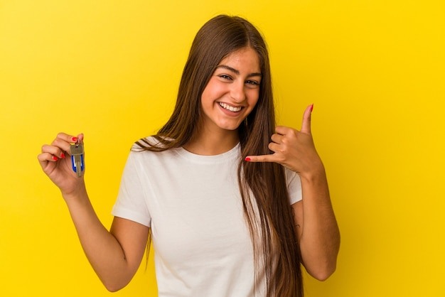 Mujer caucásica joven que sostiene una llave de la casa aislada en fondo amarillo que muestra un gesto de la llamada del teléfono móvil con los dedos.