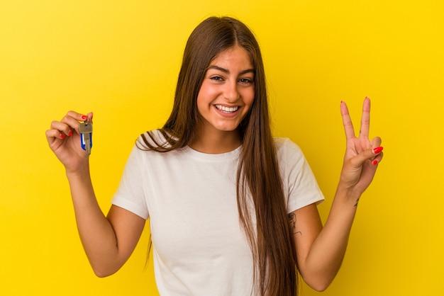 Mujer caucásica joven que sostiene una llave de la casa aislada en fondo amarillo que muestra el número dos con los dedos.
