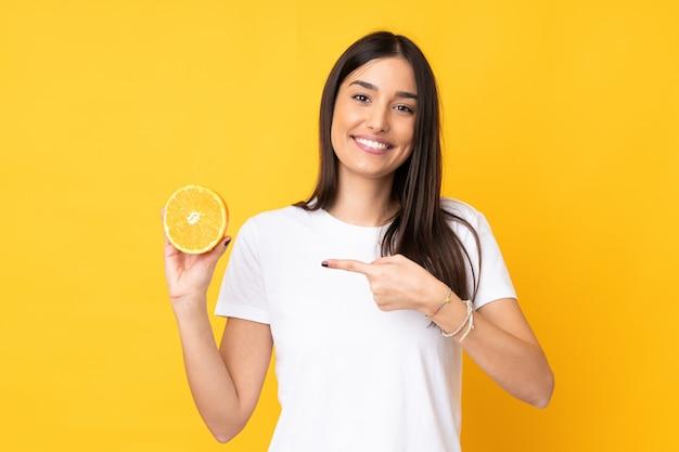 Mujer caucásica joven que sostiene una naranja aislada en la pared amarilla y que la señala