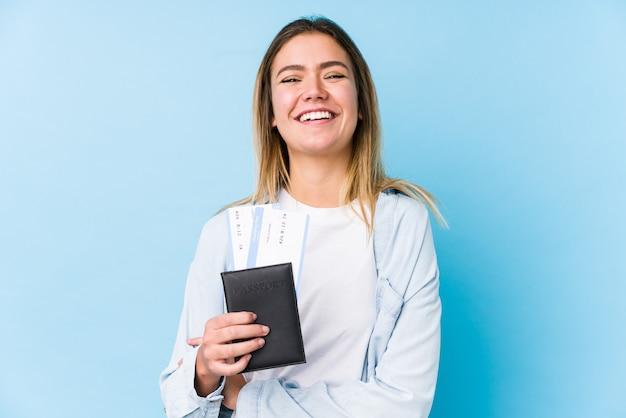 Mujer caucásica joven que sostiene un pasaporte aislado riendo y divirtiéndose.