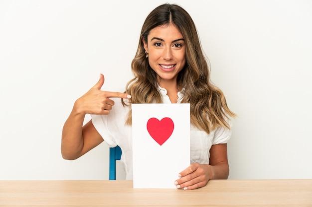 Mujer caucásica joven que sostiene una persona aislada de la tarjeta del día de san valentín que señala con la mano a un espacio de la copia de la camisa, orgulloso y confiado