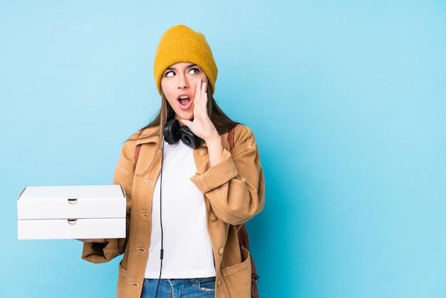 La mujer caucásica joven que sostiene las pizzas aisladas está diciendo una noticia secreta de frenado caliente y está mirando a un lado