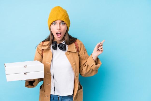 Mujer caucásica joven que sostiene las pizzas aisladas que señalan al lado