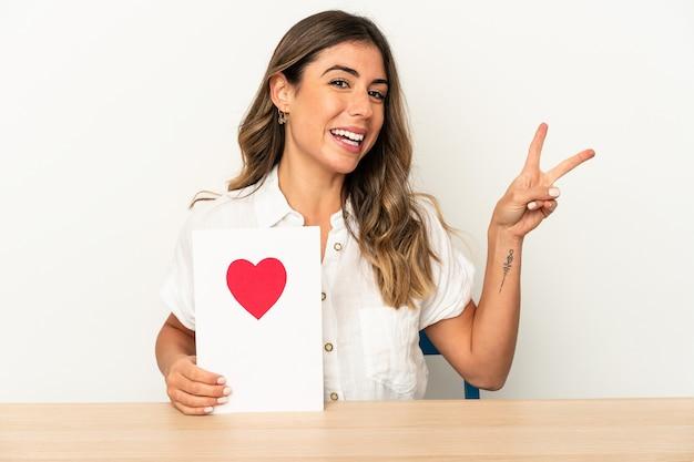 Mujer caucásica joven que sostiene una tarjeta del día de san valentín aislada alegre y despreocupada que muestra un símbolo de paz con los dedos.