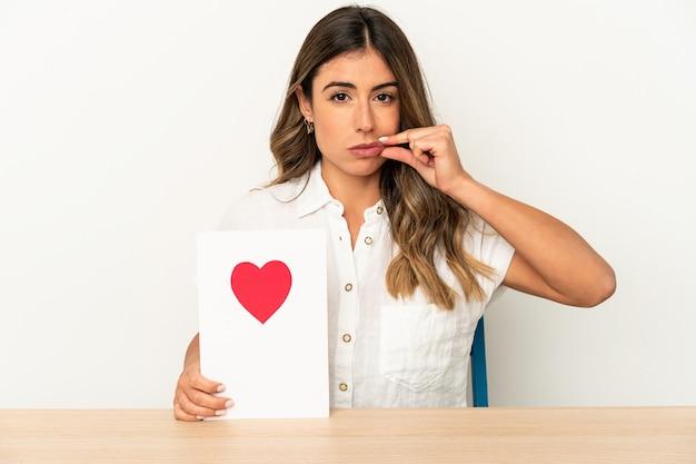 Mujer caucásica joven que sostiene una tarjeta del día de san valentín aislada con los dedos en los labios que guardan un secreto.