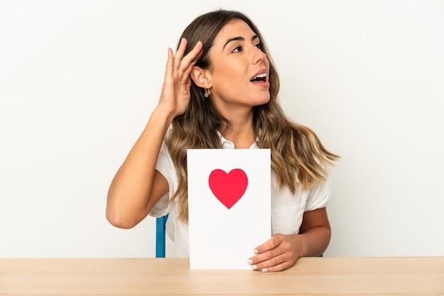Mujer caucásica joven que sostiene una tarjeta del día de san valentín aislada que intenta escuchar un chisme.