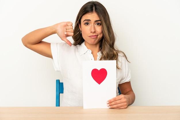Mujer caucásica joven que sostiene una tarjeta del día de san valentín aislada que muestra un gesto de aversión, pulgares hacia abajo. concepto de desacuerdo.