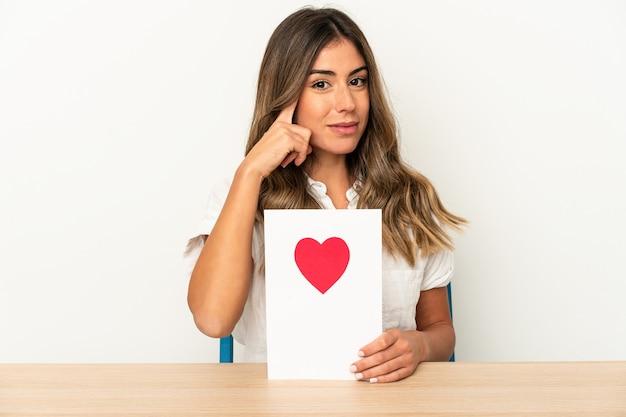 Mujer caucásica joven que sostiene una tarjeta del día de san valentín aislada que señala el templo con el dedo, pensando, centrado en una tarea.