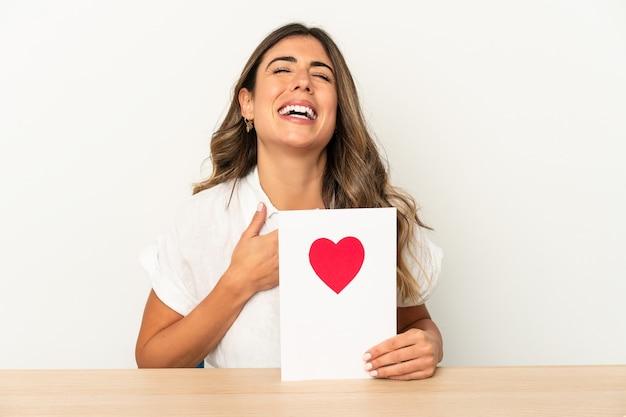 Mujer caucásica joven que sostiene una tarjeta del día de san valentín aislada se ríe en voz alta manteniendo la mano en el pecho.