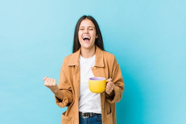Mujer caucásica joven que sostiene una taza de café que anima despreocupado y emocionado. concepto de victoria
