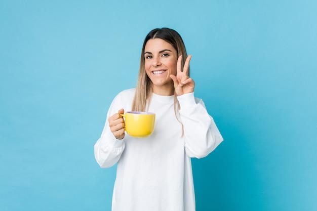 Mujer caucásica joven que sostiene una taza de café que muestra la muestra de la victoria y que sonríe ampliamente.