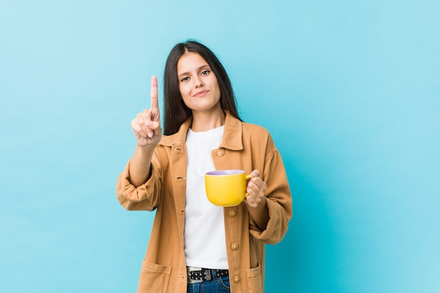 Mujer caucásica joven que sostiene una taza de café que muestra el número uno con el dedo.