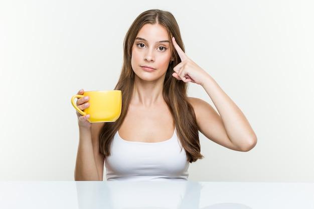 Mujer caucásica joven que sostiene una taza que señala su sien con el dedo, pensando, centrado en una tarea.