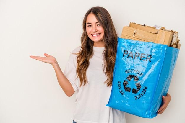 Mujer caucásica joven reciclando papel aislado sobre fondo blanco mostrando un espacio de copia en una palma y sosteniendo otra mano en la cintura.