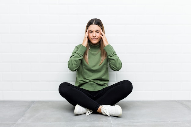 Mujer caucásica joven sentada en el suelo tocando las sienes y tener dolor de cabeza.