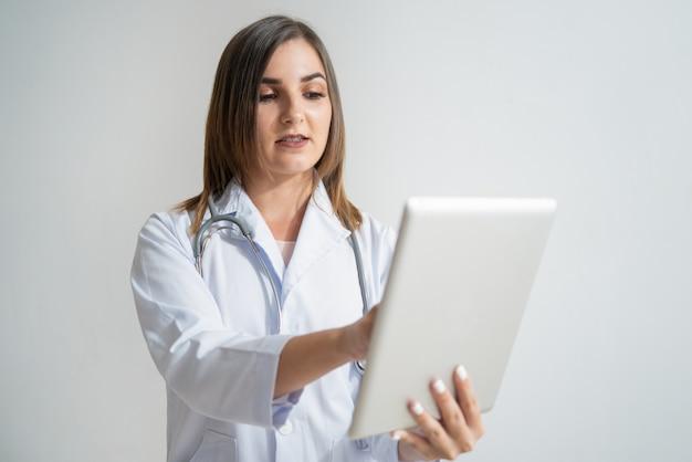 Mujer caucásica joven seria en la capa del laboratorio que mira la tableta