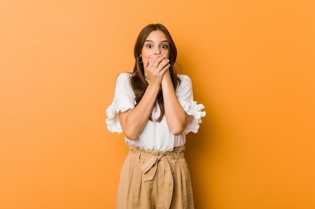 Mujer caucásica joven sorprendida cubriendo la boca con las manos.