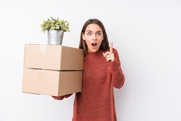 Mujer caucásica joven sosteniendo cajas aisladas teniendo una idea, concepto de inspiración.