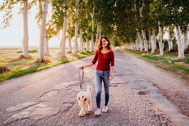 Mujer caucásica joven con su perro caniche en un automóvil