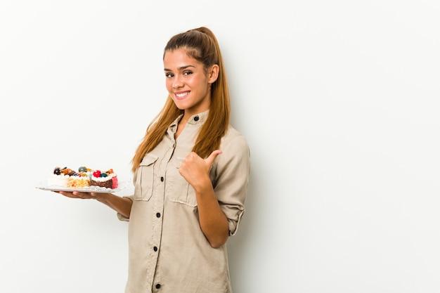 Mujer caucásica joven con tortas dulces sonriendo y levantando el pulgar