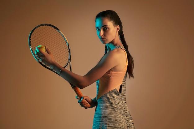Una mujer caucásica jugando al tenis aislado sobre fondo marrón en luz mixta y neón. colocar joven jugadora en movimiento o acción durante el juego deportivo. concepto de movimiento, deporte, estilo de vida saludable.